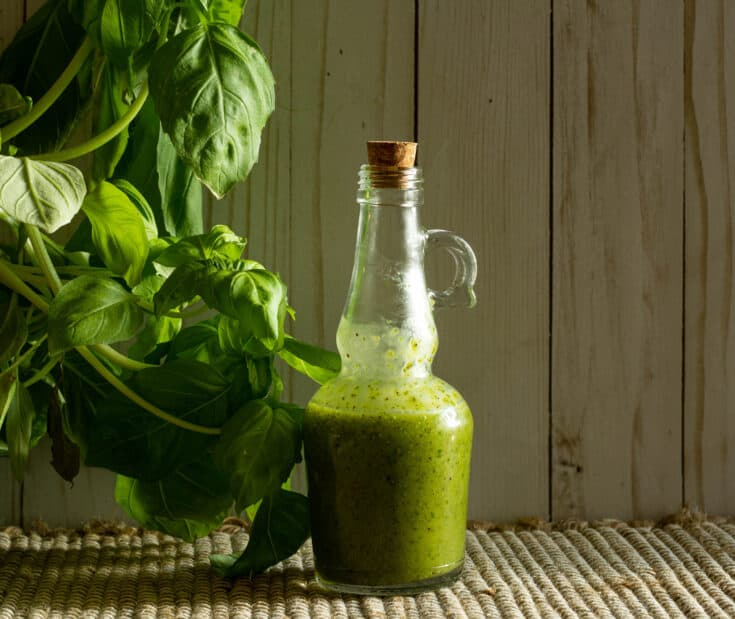 Bottle of salad dressing next to a basil plant