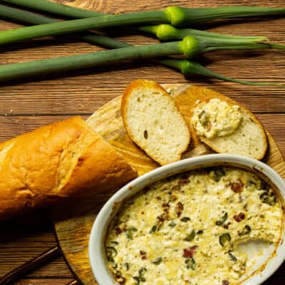 baguette on a board with a dish of leek scape dip