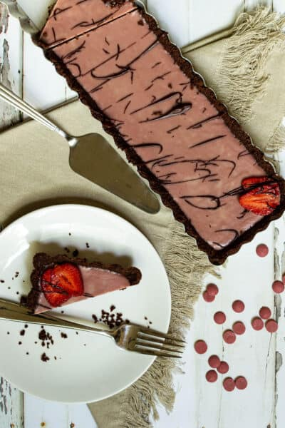 ruby chocolate tart next to a plate with a piece of tart