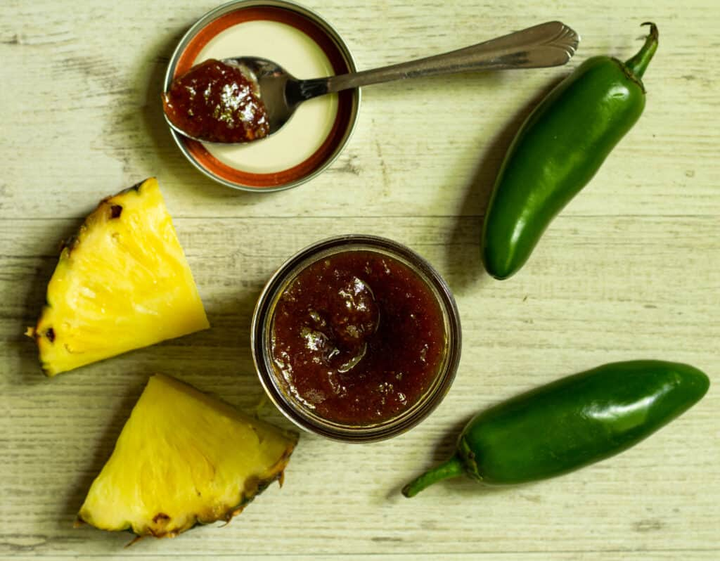 overhead view of barbeque sauce with pieces of fresh pineapple and jalapeno