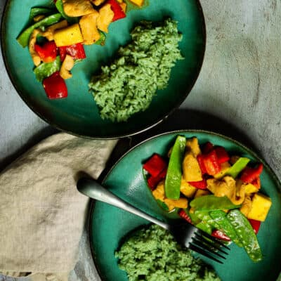two green bowls of chicken and pineapple stirfry with bamboo rice