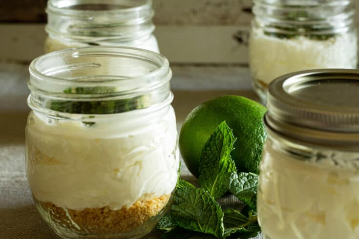 Jars of no bake cheesecake next to fresh mint and a lime