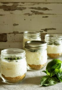 jars of no bake chhesecake with a lime and fresh mint
