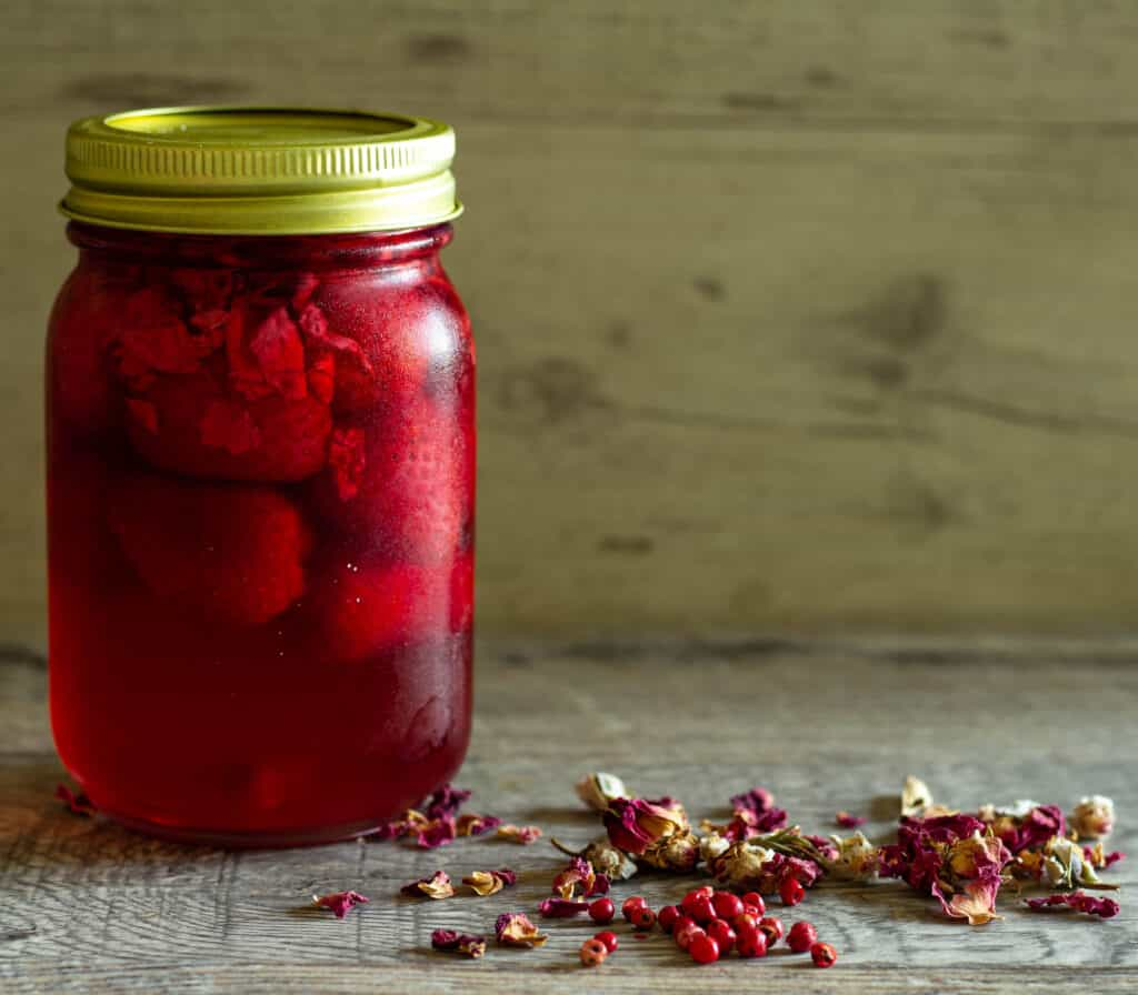 Jar of pickled strawberries next to dried rose petals and pink peppercorns