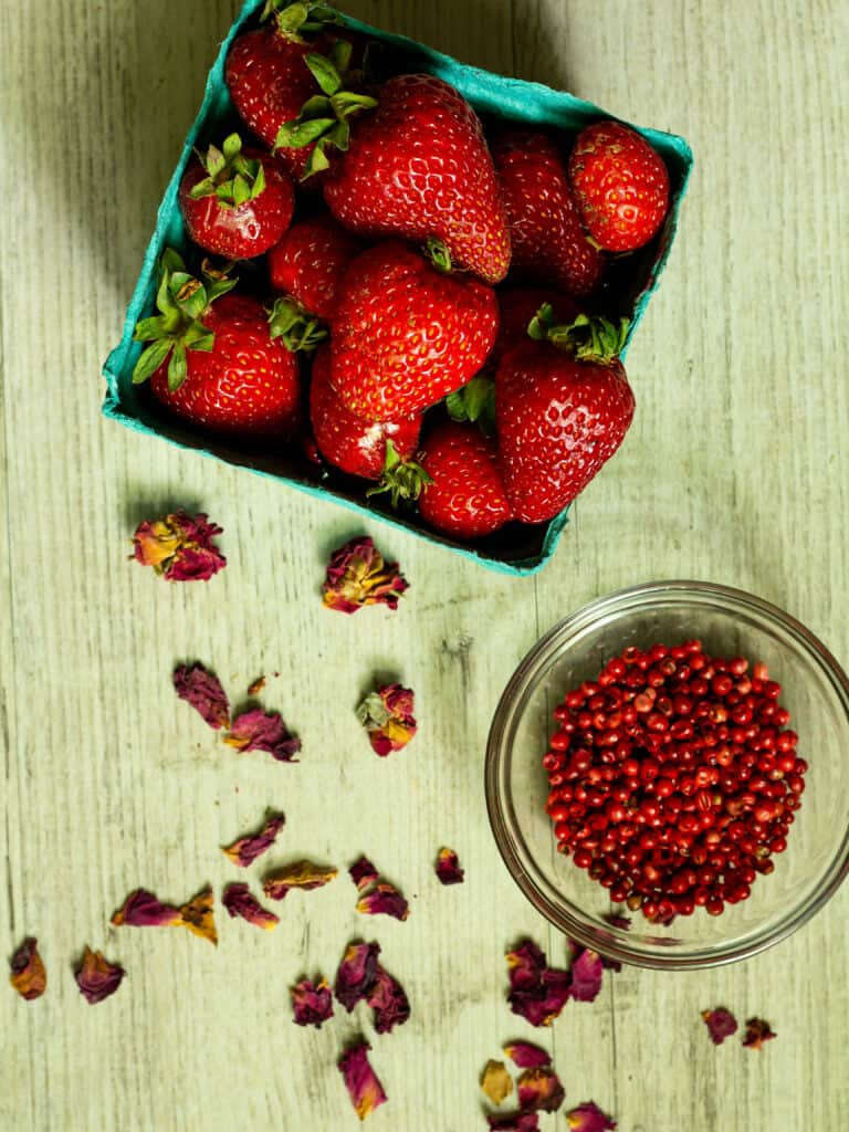 basket of strawberries next to rose petals and pink peppercorns