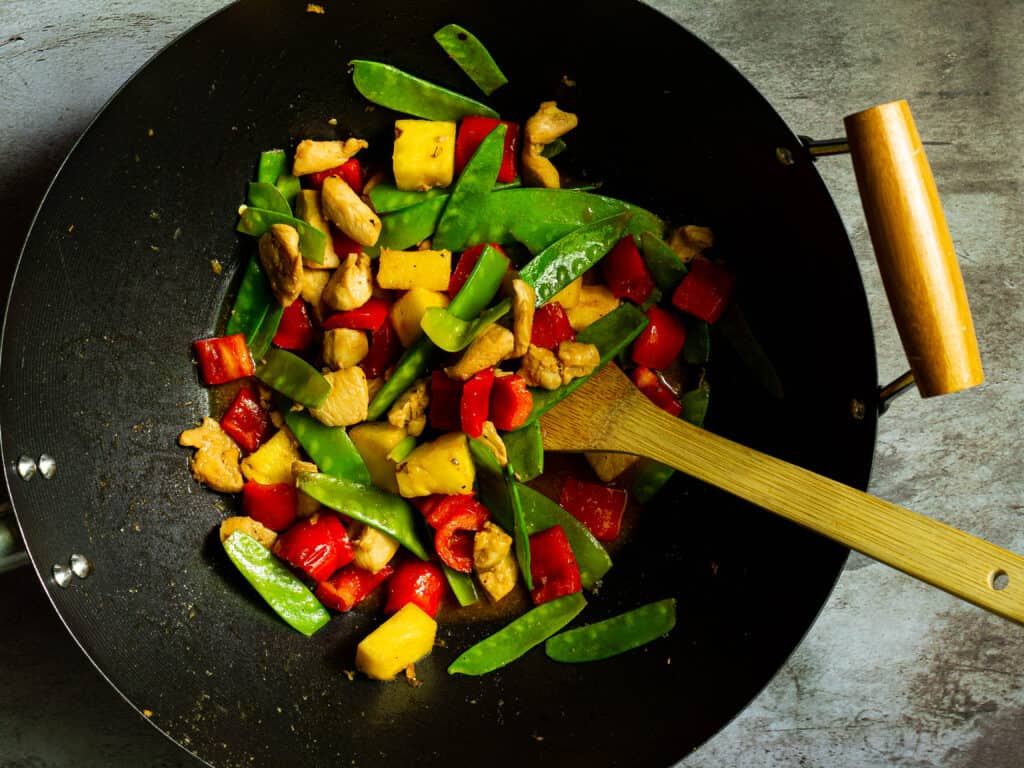 stir fry in a wok with a bamboo spatula