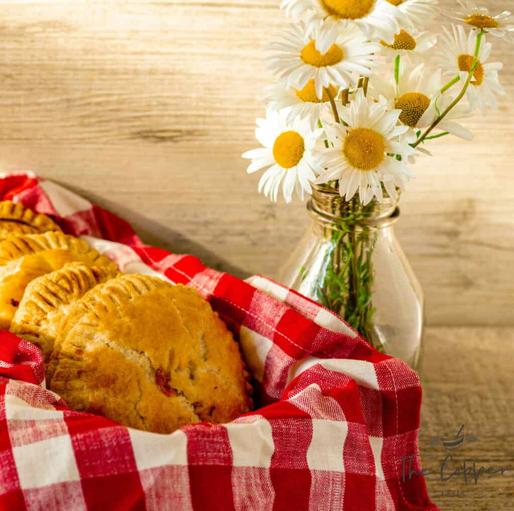 Hand pies next to a vase of daisies