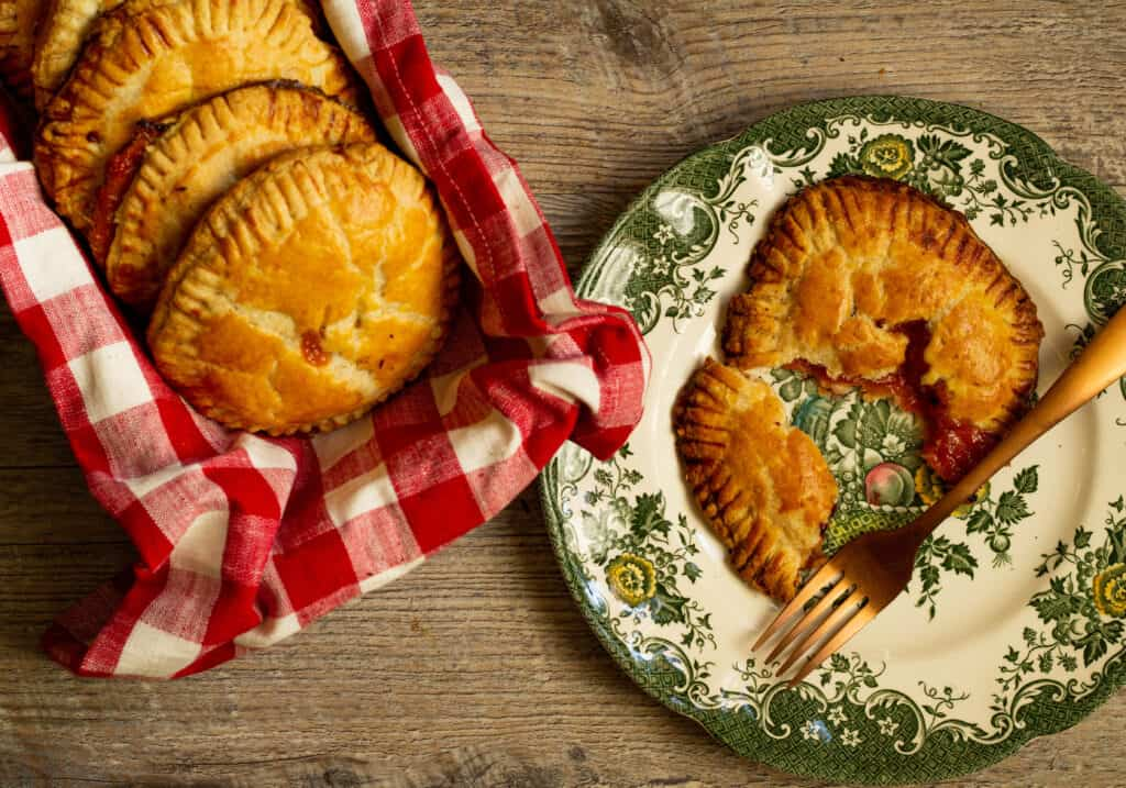 hand pies in a red and white dish towel next to a plate with a hand pie and fork