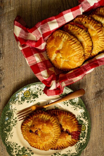 Hand pies on a plate next to hand pies in a dish wrapped in a red and white checked towel