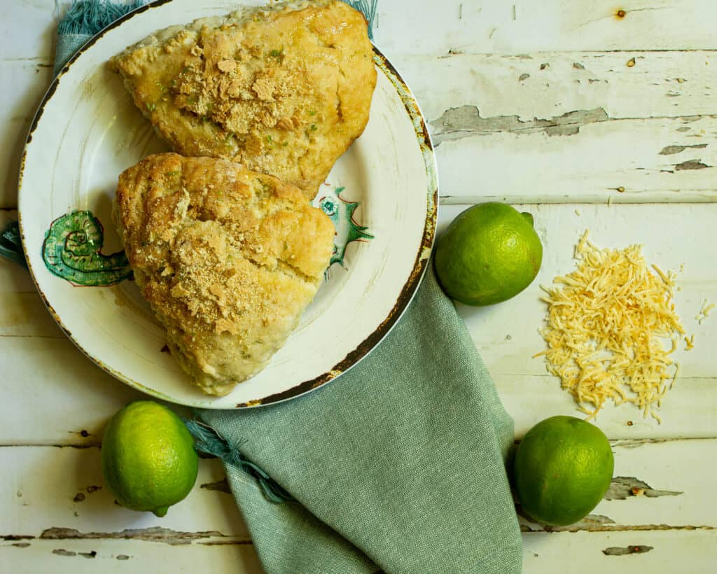 two scones on a white plate with limes and toasted coconut