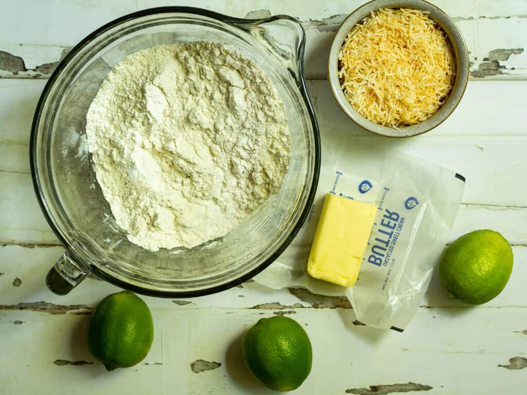 bowl of flour with butter, limes, and toasted coconut