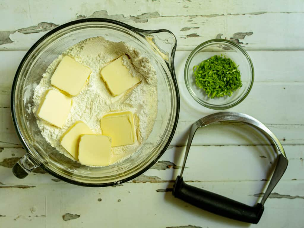bowl of flour with butter in the bowl and lime zest