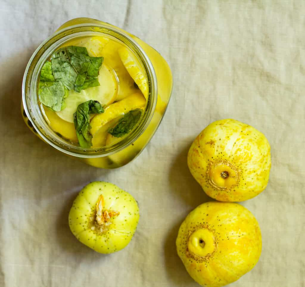overhead view of a jar of lemon cucumber pickles with three lemon cucumbers