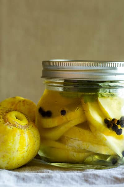 jar of lemon cucumbers next to lemon cucumbers