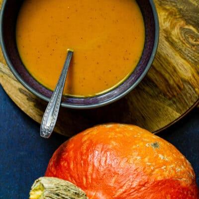 closeup photo of red kuri squash soup in a blue bowl
