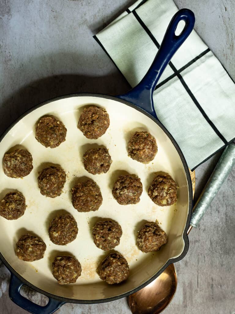 meatballs in a large skillet with a dish towel and spoon