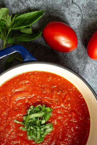 tomato sauce in a stock pot with fresh chopped basil