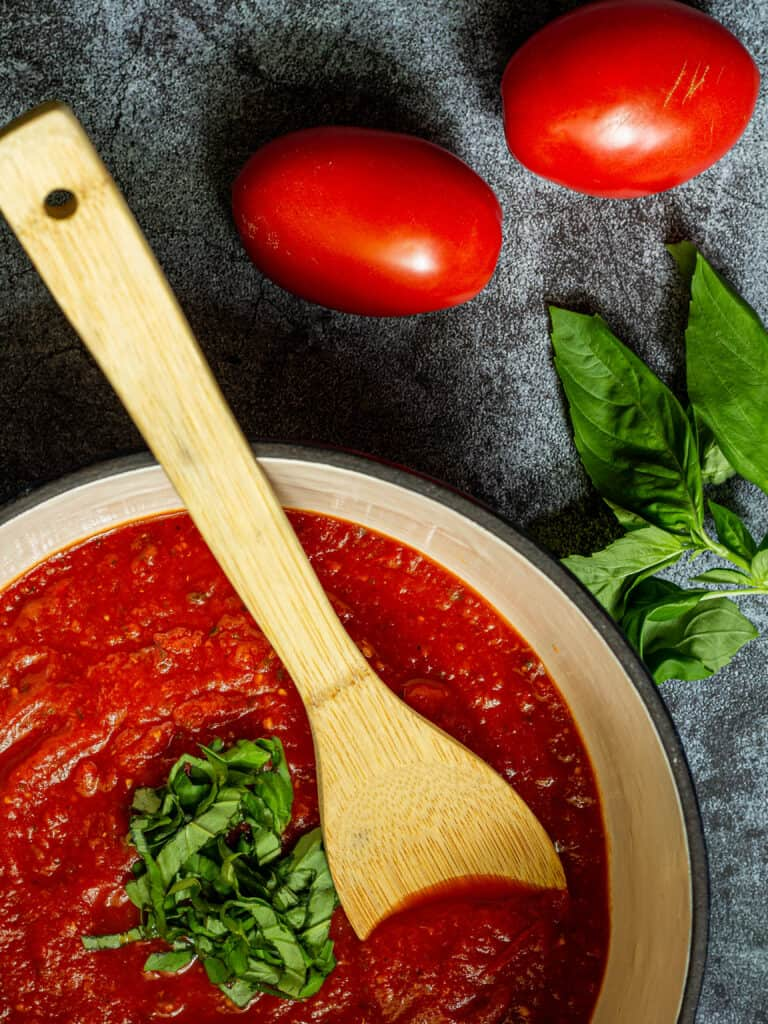 pot of marinara sauce with a wooden spoon on a blue background